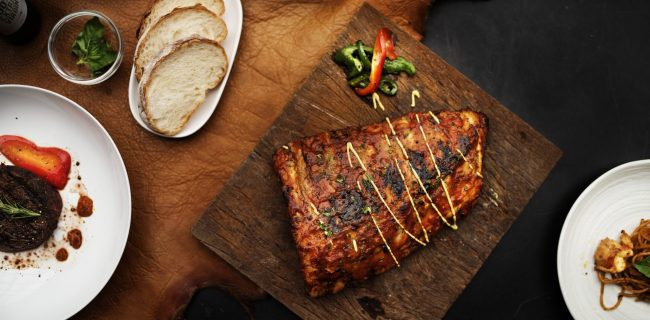 Closeup of pork ribs steak on wooden board food styling